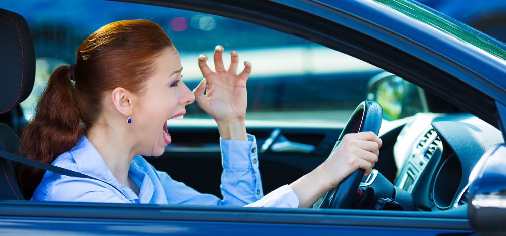 Angry woman with ginger hair is frustrated at the worst driving habits of other road users