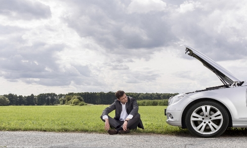 A man sitting on the ground next to his broken down car