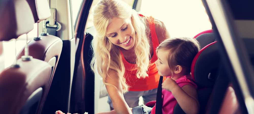 Blonde mother straps child into booster seat in car