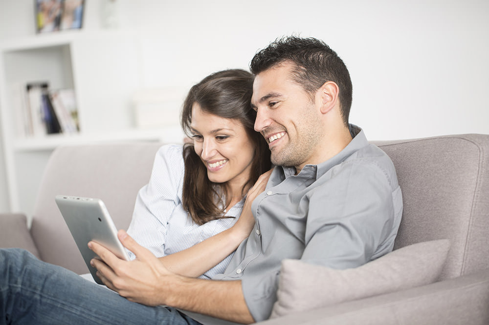 Smiling couple looking for guaranteed car finance online