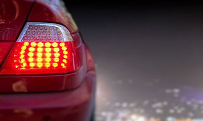 Close up of a red car with indicator light on