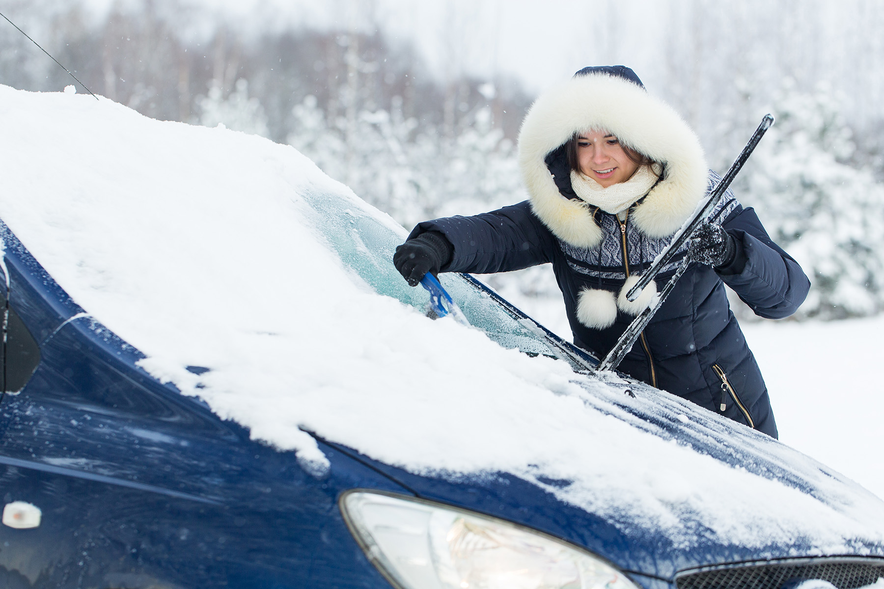 Woman clearing snow and ice from her car
